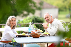 Couple eating on terrace on sunny day Stock Photo