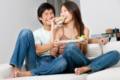 Couple Eating Together. A good looking couple having a sandwich on their couch at home royalty free stock photo