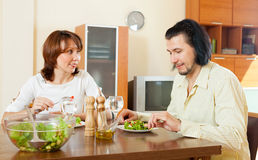 Couple eating vegetables and herbs in the home Stock Images