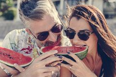 Couple eating watermelon at the beach royalty free stock image