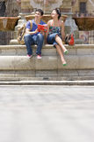 Couple on edge of fountain with guide book, smiling, low angle view Stock Photos