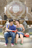 Couple on edge of fountain looking at guide book, smiling Stock Photo