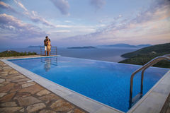 Couple on edge of infinity pool. Overlooking blue waters with dramatic skies in purple hues Stock Photography