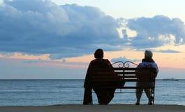Couple. Elder couple couple sitting on a seaside bench enjoying the sunset over the sea Royalty Free Stock Image