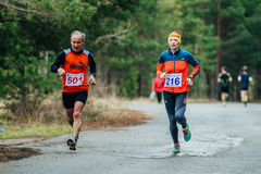 Couple  elderly athletes men and a girl running down road Royalty Free Stock Photo