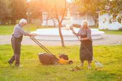 Couple of elderly gardeners working. Lawn mower and rake. How to keep garden clean Royalty Free Stock Photo