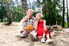 Couple of elderly people feeling thoughtful and inspired sitting on beach stock photos