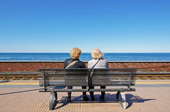 Couple of elderly people relax enjoying the beautiful view. A couple of elderly people relax enjoying the beautiful view while sitting on a bench waiting for the Royalty Free Stock Photography