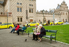 Couple of elderly tourists sit on the bench. PRAGUE: Couple of elderly tourists sit on the bench and read a guidebook about old city in Czech Republic. Prague Royalty Free Stock Image