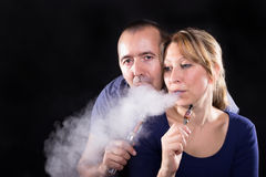 Couple with electronic cigarettes Royalty Free Stock Photos