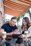 Couple with electronic device at a cafe. Portrait of beautiful cheerful young couple in casual clothes sitting in street cafe with wicker furniture sharing Royalty Free Stock Image