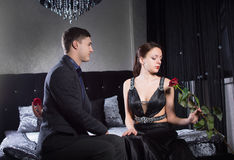 Couple in Elegant Outfits Sitting at the Bedroom Royalty Free Stock Photography