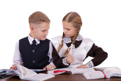 A couple of elementary school students sit at a desk Stock Image