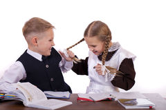 A couple of elementary school students sit at a desk Stock Photo