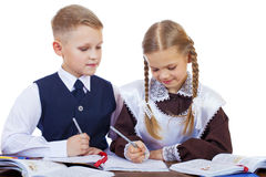 A couple of elementary school students sit at a desk Stock Images