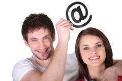 Couple with email symbol. Couple holding up the email symbol Stock Photo