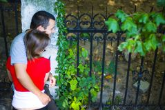 Couple in embrace. A young couple share a hug in a corner of a park, turning to their side to look at something Stock Photos