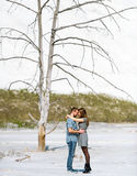 Couple embrace against white mountains and lonely dry tree. Stock Photography