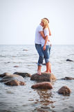 Couple embrace on a stone in sea Stock Image