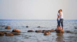 Couple embrace on a stone in sea Stock Photography
