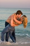 Couple Embrace In The Surf. A young couple wearing bluejeans embrace in the surf at sunset royalty free stock photo
