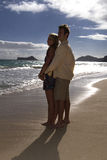 Couple embrace on a tropical beach Stock Images