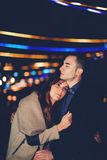 The couple embrace and waiting Christmas fireworks. Portrait of beautiful romantic couple embracing at outdoor night event with beautiful lights on background stock image