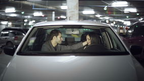 Couple embraces in the car at underground parking.  stock footage