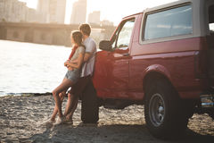 Couple embracing on beach. And leaning back on classical car Stock Photography