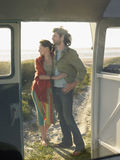 Couple Embracing On Beach View Through Campervan Door Stock Photography