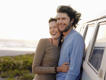 Couple Embracing By Campervan On Beach. Smiling young couple embracing by campervan on beach stock images