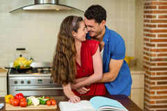 Couple embracing while checking the recipe book Royalty Free Stock Photography
