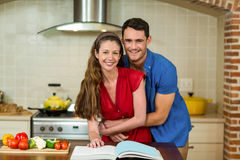 Couple embracing while checking the recipe book Stock Photo