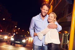 Couple embracing on city street at night, portrait Stock Photography