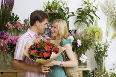Couple embracing beside display in flower shop, holding bouquet of red flowers, smiling, side view Stock Image