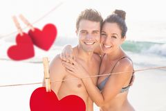 Couple embracing each other at beach with hanging hearts around Stock Photo