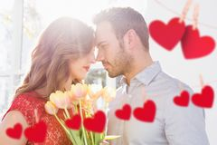 Couple embracing each other with red hanging hearts Stock Image