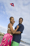 Couple Embracing While Flying Kite On The Beach. Portrait of an African American couple embracing while flying kite on the beach royalty free stock photos