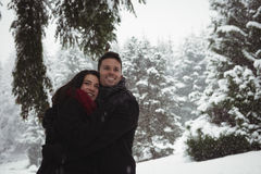 Couple embracing in forest during winter Stock Photo