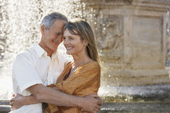 Couple Embracing By Fountain Royalty Free Stock Image