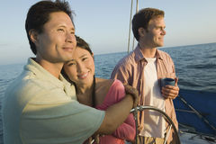 Couple Embracing By Friend On Sailboat Royalty Free Stock Image