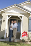 Couple Embracing In Front Of House For Sale Royalty Free Stock Photography