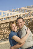 Couple Embracing In Front Of Incomplete House. Portrait of happy mature couple embracing in front of incomplete house royalty free stock image