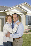 Couple Embracing In Front Of New House Stock Photography