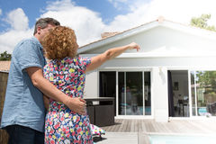 Couple embracing in front of new modern house, back view Stock Images