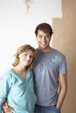Couple Embracing In Front Of Partially Painted Wall stock photo