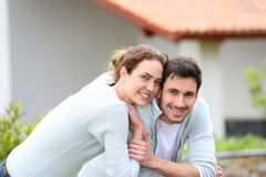 Couple embracing in front of their home Stock Images