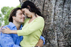 Couple embracing in front of tree Stock Photo