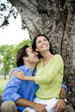 Couple embracing in front of tree Royalty Free Stock Images