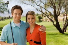 Couple embracing on golf course Stock Photography